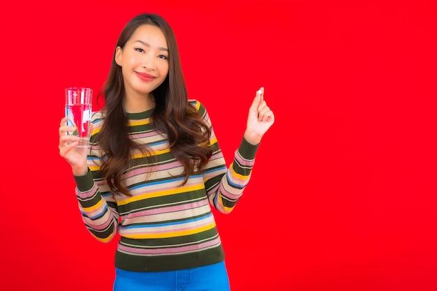 Portret mooie jonge aziatische vrouw met drinkwater en pil op rode muur Gratis Foto