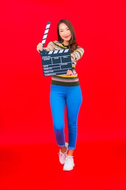 Portret mooie jonge aziatische vrouw met filmlei die op rode geïsoleerde muur knipt Gratis Foto