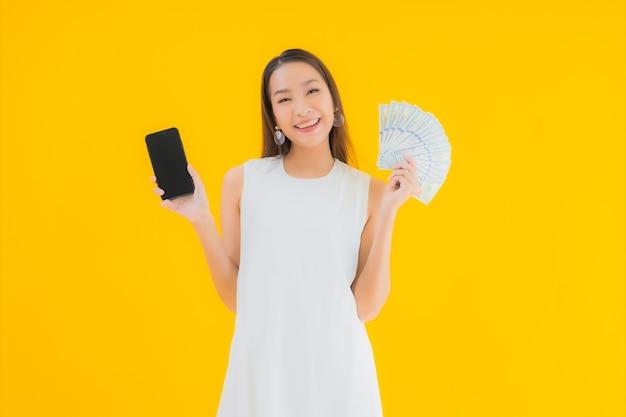 Portret mooie jonge aziatische vrouw met geld contant Gratis Foto