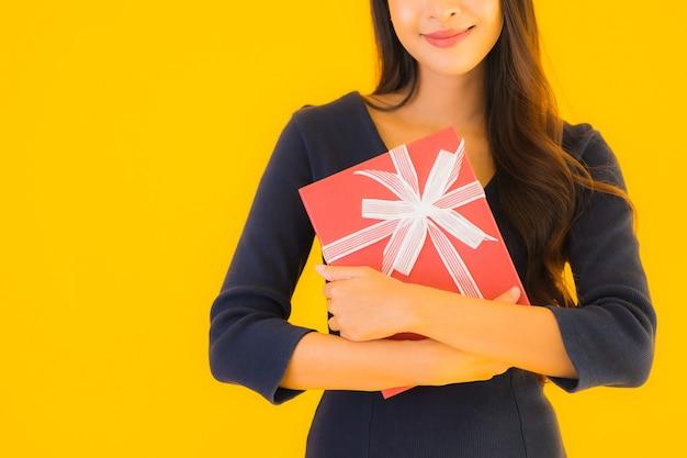 Portret mooie jonge aziatische vrouw met geschenkdoos Gratis Foto