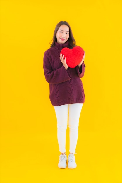 Portret mooie jonge aziatische vrouw met hart kussen vorm Gratis Foto