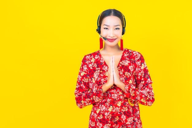Portret mooie jonge aziatische vrouw met hoofdtelefoon voor de zorg van het klantencall centre op gele muur Gratis Foto