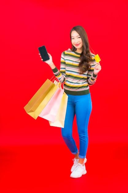 Portret mooie jonge aziatische vrouw met kleurrijke boodschappentas en creditcard op rode muur Gratis Foto