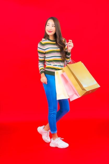 Portret mooie jonge aziatische vrouw met kleurrijke boodschappentas op rode muur Gratis Foto