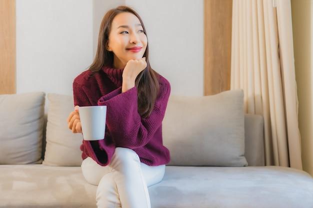 Portret mooie jonge aziatische vrouw met koffiekop op het binnenland van de bankdecoratie van woonkamer Gratis Foto