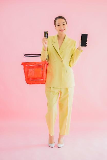 Portret mooie jonge aziatische vrouw met kruidenierswinkelmandje van supermarkt op kleur Gratis Foto