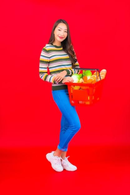 Portret mooie jonge aziatische vrouw met kruidenierswinkelmandje van supermarkt op rode geïsoleerde muur Gratis Foto
