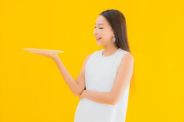 Portret mooie jonge aziatische vrouw met lege schotel en plaat Gratis Foto