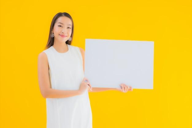 Portret mooie jonge aziatische vrouw met lege witte aanplakbiljet of poster Gratis Foto