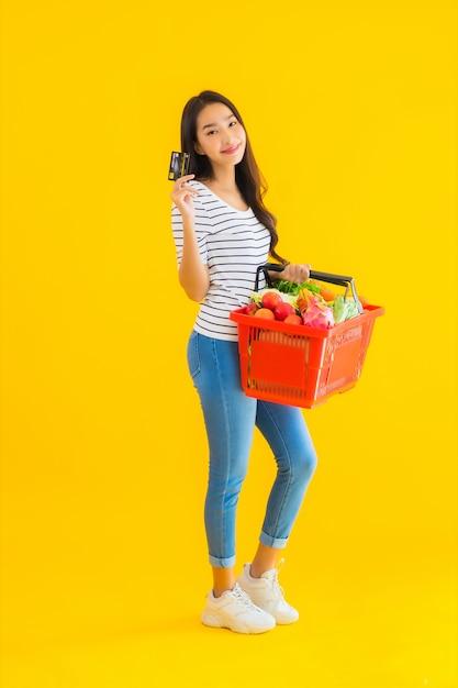 Portret mooie jonge aziatische vrouw met mand kruidenier en kar van supermarkt Gratis Foto