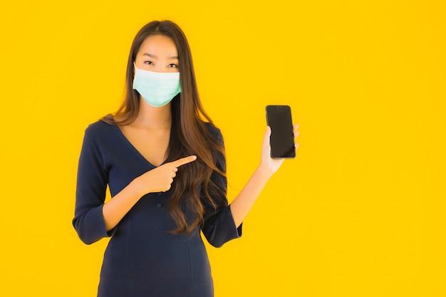 Portret mooie jonge aziatische vrouw met masker en telefoon Gratis Foto