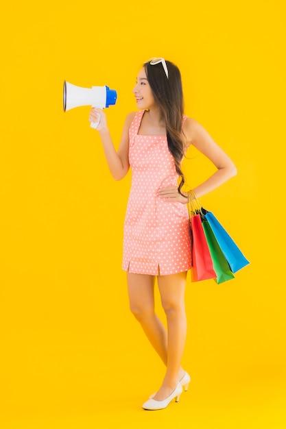 Portret mooie jonge aziatische vrouw met megafoon en boodschappentas Gratis Foto