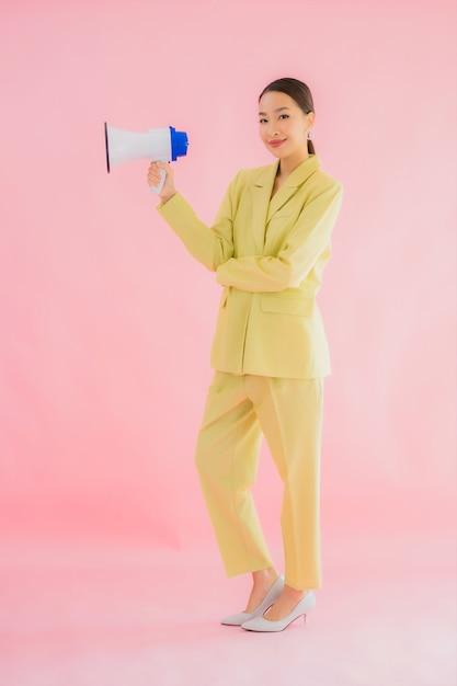 Portret mooie jonge aziatische vrouw met megafoon op kleur Gratis Foto