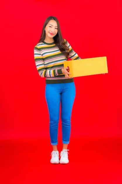 Portret mooie jonge aziatische vrouw met pakketdoos op rode geïsoleerde muur Gratis Foto