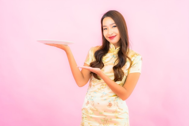 Portret mooie jonge aziatische vrouw met plaat op roze kleurenmuur Gratis Foto