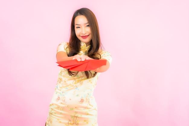 Portret mooie jonge aziatische vrouw met rode enveloppen op roze muur Gratis Foto