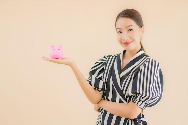 Portret mooie jonge aziatische vrouw met roze spaarvarken Gratis Foto