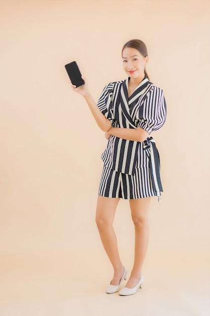 Portret mooie jonge aziatische vrouw met slimme mobiele telefoon Gratis Foto