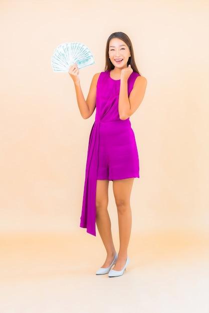 Portret mooie jonge aziatische vrouw met veel contant geld en geld op kleurenachtergrond Gratis Foto