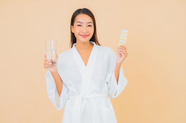 Portret mooie jonge aziatische vrouw met waterglas en drugpil op beige Gratis Foto