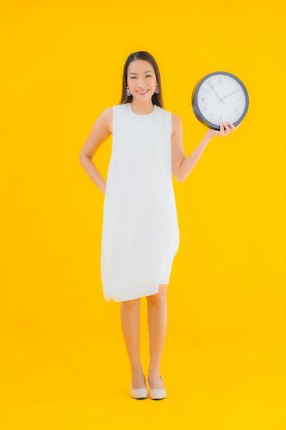 Portret mooie jonge aziatische vrouw met wekker of klok Gratis Foto