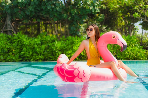 Portret mooie jonge aziatische vrouw op de flamingo opblaasbare vlotter in zwembad bij hoteltoevlucht Gratis Foto