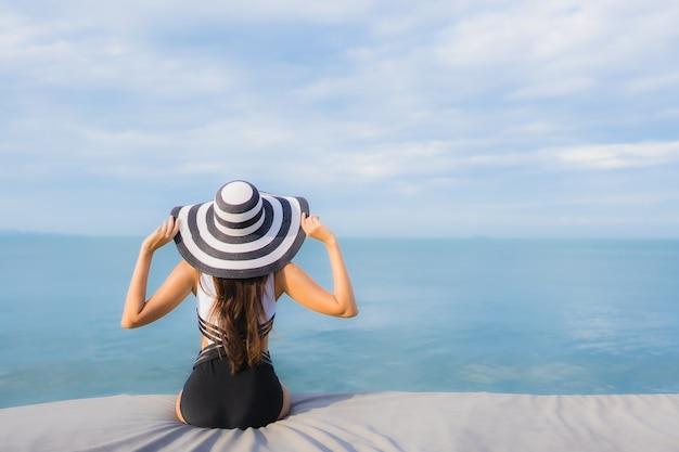 Portret mooie jonge aziatische vrouw rond overzeese strandoceaan Gratis Foto