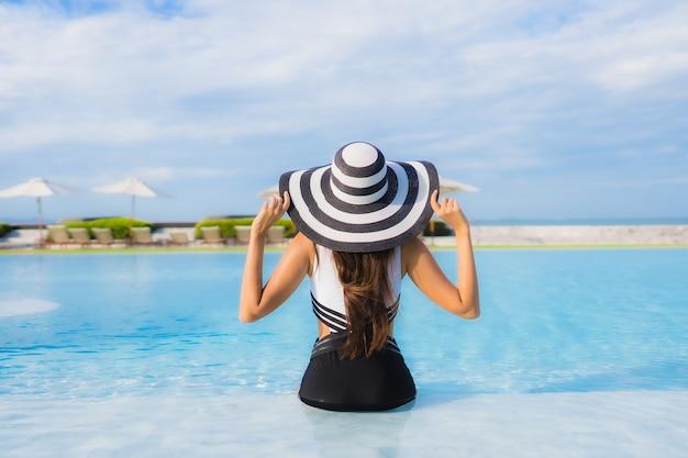 Portret mooie jonge aziatische vrouw rond zwembad Gratis Foto