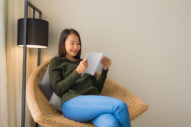Portret mooie jonge aziatische vrouwen die boek lezen en op bankstoel zitten Gratis Foto
