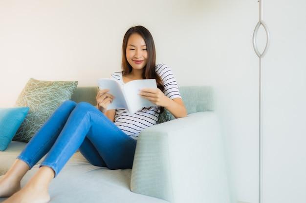 Portret mooie jonge aziatische vrouwen die boek met koffiekop lezen Gratis Foto