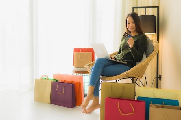 Portret mooie jonge aziatische vrouwen die computerlaptop met creditcard voor online het winkelen met behulp van Gratis Foto