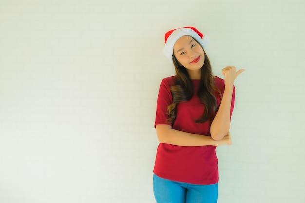 Portret mooie jonge aziatische vrouwen die santahoed dragen voor viering in kerstmis Gratis Foto
