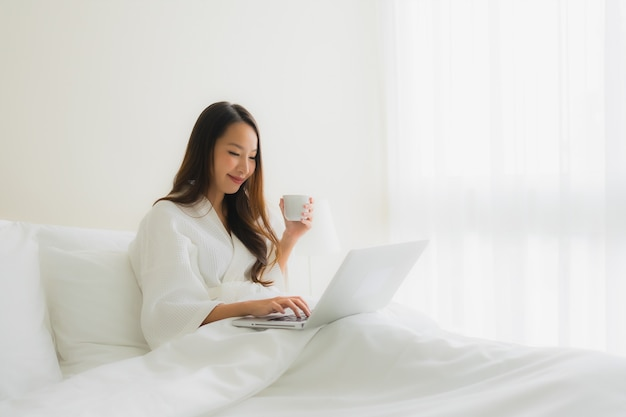 Portret mooie jonge aziatische vrouwen met koffiekop en computerlaptop op bed Gratis Foto