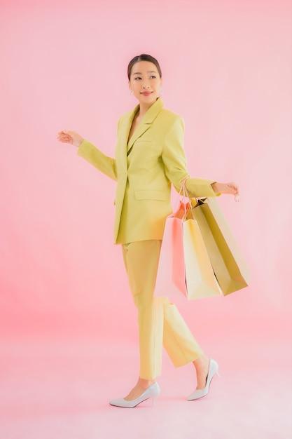 Portret mooie jonge aziatische zakenvrouw met boodschappentas op kleur geïsoleerd Gratis Foto