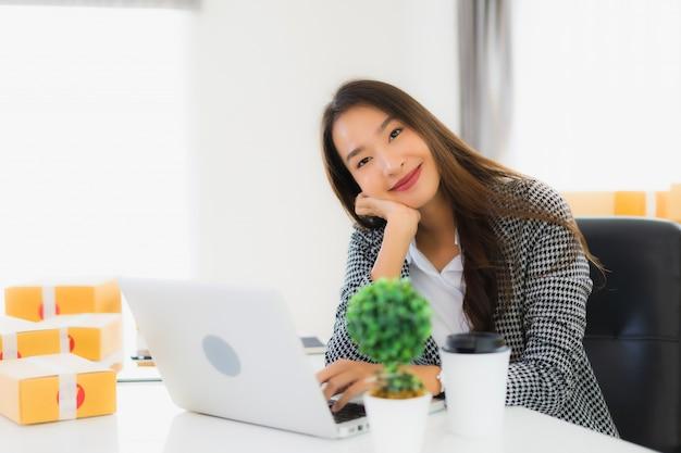 Portret mooie jonge aziatische zakenvrouw werken vanuit huis met laptop mobiele telefoon met kartonnen doos klaar voor verzending Gratis Foto