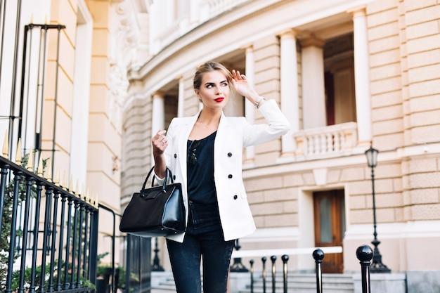 Portret mooie vrouw in witte jas lopen op straat. ze glimlacht naar haar kant. Gratis Foto