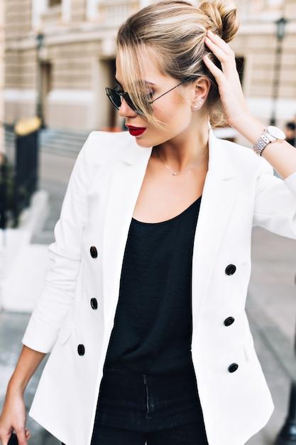 Portret mooie vrouw in zonnebril op straat. ze raakt haar aan en kijkt naar beneden. Gratis Foto