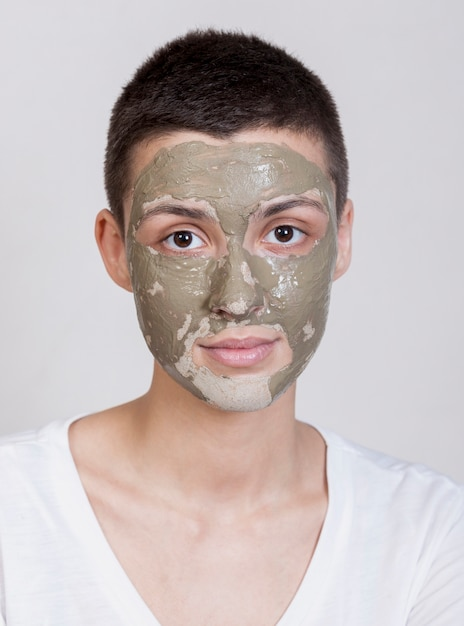 Portret mooie vrouw met modderbehandeling op gezicht Gratis Foto
