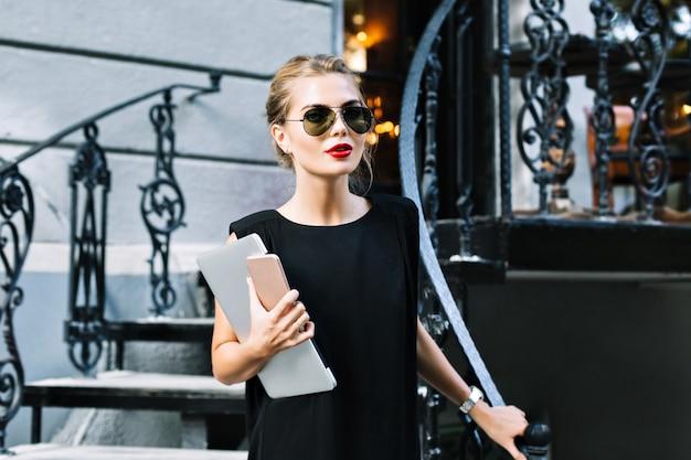 Portret mooie zakenvrouw in zwarte jurk op trappen buiten. ze kijkt naar de camera. Gratis Foto