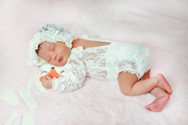 Portret schattig van kleine aziatische pasgeboren baby slapen op pluizig zacht bed. Premium Foto