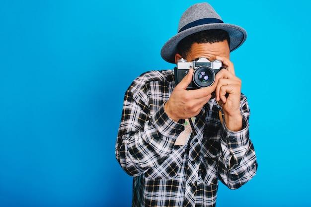 Portret stijlvolle jonge man in hoed foto op camera maken. tavelling, weekends, vakanties, opgewonden, toeristisch, echte positieve emoties uiten, plezier maken. Gratis Foto