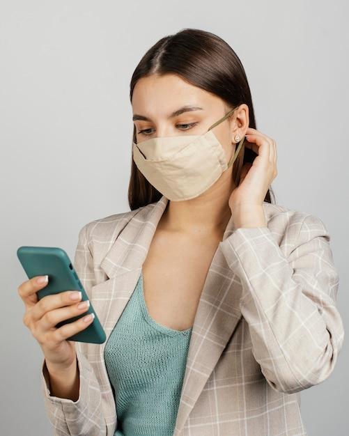 Portret stijlvolle vrouw met masker met behulp van mobiel Gratis Foto