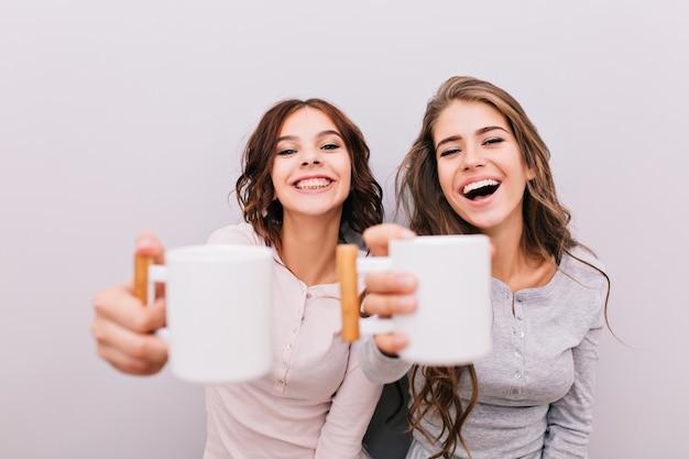 Portret twee grappige meisjes in pyjama's plezier op grijze muur. ze strekten witte kopjes uit en lachten. Gratis Foto