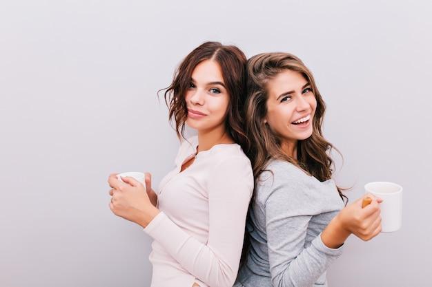Portret twee jonge meisjes in pyjama's met kopjes op grijze muur. ze staan rug aan rug en glimlachen. Gratis Foto