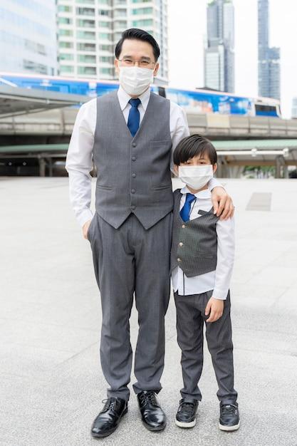 Portret vader en zoon dragen beschermend gezichtsmasker voor bescherming tijdens de quarantaine Gratis Foto