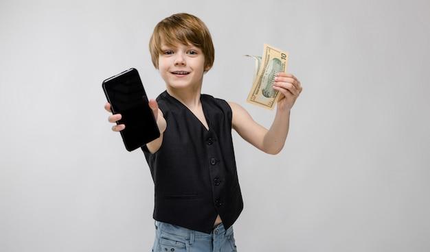 Portret van aanbiddelijke grappige kleine jongen die zich in zwart vest bevinden die mobiele telefoon en geld op grijs houden Premium Foto