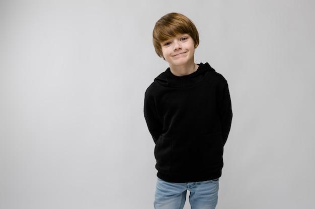 Portret van aanbiddelijke smilling kleine jongen die zich op grijze muur bevindt Premium Foto