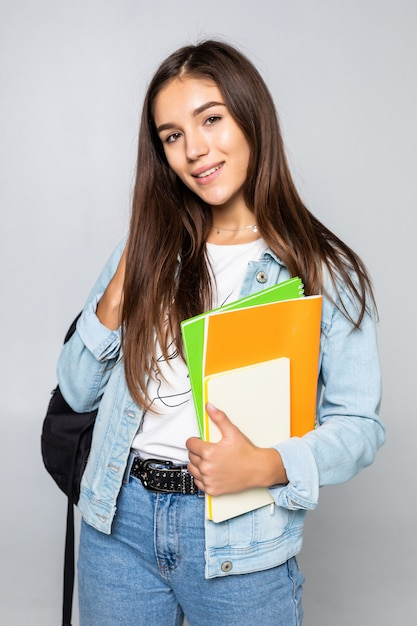 Portret van aantrekkelijk leuk jong studentenmeisje dat op witte muur wordt geïsoleerd Gratis Foto