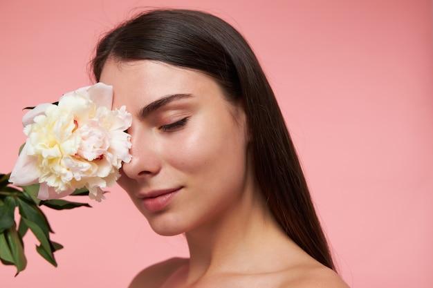 Portret van aantrekkelijk, leuk ogend meisje met lang donkerbruin haar en een gezonde huid, haar oog aanraken met een bloem, dromen met gesloten ogen. stand geïsoleerd, close-up over pastel roze muur Gratis Foto
