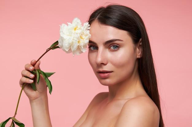 Portret van aantrekkelijk, leuk ogend meisje met lang donkerbruin haar en een gezonde huid, hoofd met een bloem aan te raken. kijken, close-up, geïsoleerd over pastel roze muur Gratis Foto